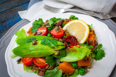 Salad with baked sweet potatoes, avocados, lentils, dried tomatoes stock photography