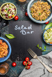 Salad bar with various healthy vegetarian salads dish, forg and black chalkboard, top view, frame. Inscription salad bar on blank Stock Photos