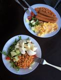 Salad with beans and sausages. Two plates with healthy salad with beans annd one with three sausages Royalty Free Stock Photos