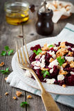 Salad of beetroot, feta and walnuts with leaves of parsley on the old wooden background. Stock Photo