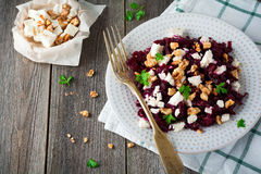 Salad of beetroot, feta and walnuts with leaves of parsley on the old wooden background. Stock Images