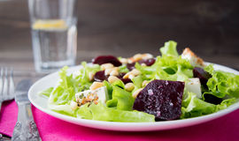 Salad with beetroot. Green salad with beetroot, feta cheese and pine nuts Royalty Free Stock Photos