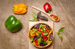 Salad from bell pepper and basil in a wooden bowl Royalty Free Stock Photos