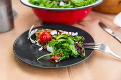 Salad with tomato,lettuce, cheese and balsamico. Salad on black plate with fork and in red bowl on table. Tomato,dried tomato,lettuce and spinach leaf. cheese royalty free stock photos