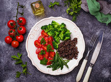 Salad with black quinoa, cherry tomatoes, broccoli and arugula. Healthy vegan food royalty free stock photo