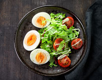 Salad with boiled eggs. On dark plate stock photos