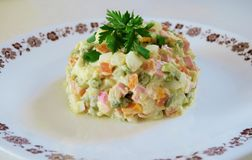 Salad of boiled vegetables, eggs, ham and parsley on a white plate close-up royalty free stock photos