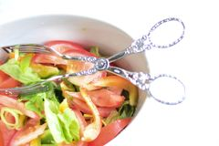 Salad bowl. With delicious salad and salad pliers Royalty Free Stock Photography