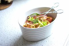 Salad bowl. With delicious salad and salad pliers Royalty Free Stock Images