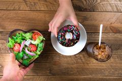Introduce the alternative of eating between donuts and salads. Salad in a bowl made of heart-shaped wood, compared to choccolate donut in white ceramic dish and stock image
