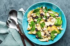 Salad bowl of spinach, apple, white cheese, nuts and cranberry Stock Photo