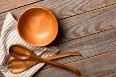 Salad bowl and wooden spoons on the wooden table Stock Image