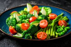 Salad with broccoli, asparagus and cherry tomatoes. Closeup of salad with broccoli, asparagus and cherry tomatoes Stock Photo