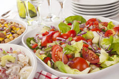 Salad Buffet. An assortment of salads on a buffet table. Potato salad, bean salad and fresh mixed salad arranged on a white table with glasses, cutlery and Royalty Free Stock Photos