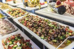 Salad buffet with a fresh bean salad in focus. Salad buffet with a large variety of salads. A fresh bean salad with cucumber and onion is in focus stock images
