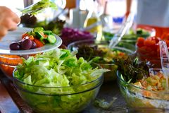 Salad buffet. The people themselves impose the desired treat Stock Images