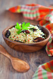 Salad of bulgur. Bulgur, dried plum, chili, parsley salad in wooden bowl on the table, selective focus Stock Images
