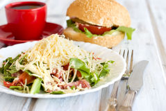 Salad, a burger and a cup of coffee for breakfast Royalty Free Stock Photography