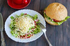 Salad, a burger and a cup of coffee for breakfast Royalty Free Stock Photo