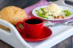 Salad, a burger and a cup of coffee for breakfast Stock Image