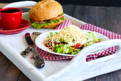 Salad, a burger and a cup of coffee for breakfast Royalty Free Stock Image