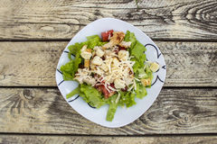 Salad `Caesar` in a plate on a wooden table. Stock Image
