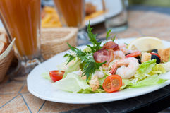 Salad in cafe. Green lettuce salad plate with prawns and baked pork rib served in cafe stock image