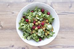 Salad of canons, raspberries, raisins, olives, nuts, carrots and pips on wooden background royalty free stock images