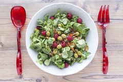Salad of canons, raspberries, raisins, olives, nuts, carrots and pips on wooden background. Red spoon and fork Stock Photo