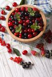 Salad of cherry, raspberry, currant and blackberry close-up. Ver. Salad of cherry, raspberry, currant and blackberry in a wooden bowl on the table close-up Stock Photos