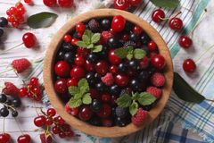Salad of cherry, raspberry, currant and blackberry horizontal to. Salad of cherry, raspberry, currant and blackberry in a wooden bowl on the table close-up Stock Photos