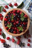 Salad of cherry, raspberry, currant and blackberry vertical top. Salad of cherry, raspberry, currant and blackberry in a wooden bowl on the table close-up Stock Photo