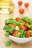 Salad and cherry tomatoes in a bowl, olive oil in the background Stock Photos