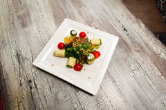 Salad with cherry tomatoes, cucumbers and orange on wood table Stock Images