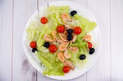 Salad with cherry tomatoes, shrimps and olives. On white plate stock images