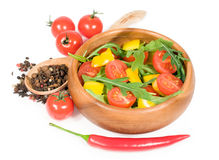 Salad with cherry tomatoes , sweet peppers and arugula in a wooden bowl Royalty Free Stock Photography