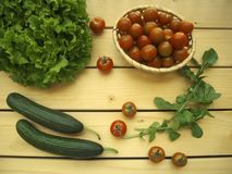 Salad, cherry tomatoes in a wicker basket, cucumbers and arugula on a wooden background. Royalty Free Stock Photo