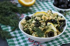 Salad with chicken, cheese and black olives in white bowls on the table stock image