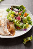 Salad and chicken on dark wood. Italian salad with rotisserie chicken and white rice dinner on a plate Royalty Free Stock Images