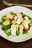 Salad with chicken and dried tomatoes. Close-up fresh salad with cornsalad, baked chicken, dried tomatoes and parmesan royalty free stock images