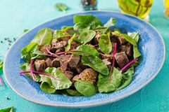 Salad of chicken liver and leaves of spinach and chard. Salad of chicken liver and leaves of spinach and chard on turquoise background Stock Images