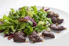 Salad with chicken liver and pine nuts on a white plate royalty free stock photos
