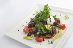 Salad with chicken liver. And poached eggs stock photos