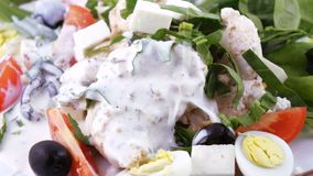 Assorted salad on lettuce leaves. Salad with chicken, olives, quail eggs, spinach, tomatoes, brynza, lemon, dressing with sour cream sauce and sprinkling with stock footage