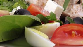 Assorted salad on lettuce leaves. Salad with chicken, olives, quail eggs, spinach, tomatoes, brynza, lemon, dressing with sour cream sauce and sprinkling with stock video footage