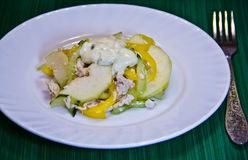 Salad with chicken and pear on a white plate. Salad with chicken, cucumber and pear on a white plate Stock Photography
