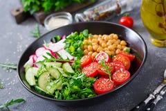 Salad of chickpeas, tomatoes, cucumbers, radish and greens. Dietary food. Buddha bowl. Vegan salad Royalty Free Stock Photo