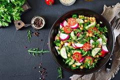Salad of chickpeas, tomatoes, cucumbers, radish and greens. Dietary food. Vegan salad. Top view. Flat lay Stock Photo