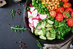 Salad of chickpeas, tomatoes, cucumbers, radish and greens. Dietary food. Vegan salad. Top view. Flat lay. Buddha bowl Stock Photo