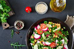 Salad of chickpeas, tomatoes, cucumbers, radish and greens. Dietary food. Vegan salad. Top view. Flat lay Stock Photography